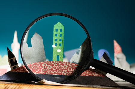 Magnifier in front of an open newspaper with paper houses. The concept of renting, searching, buying real estate. Stockfoto