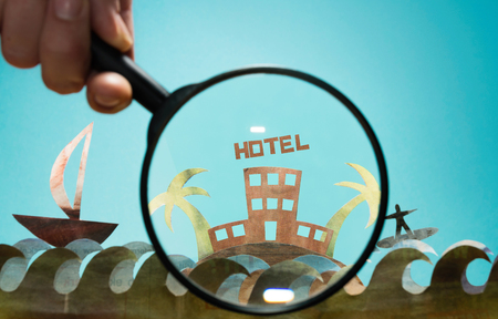 Magnifying glass in front island of paper with hotel on open newspaper. Concept of booking hotel, search tour, marketing.