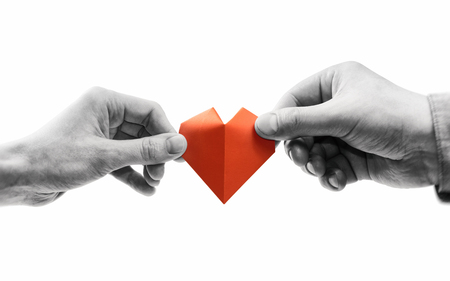 Red heart in woman and man hands. Black and white image on isolated white background. Concept of love,  giving gifts, donorship. Stockfoto