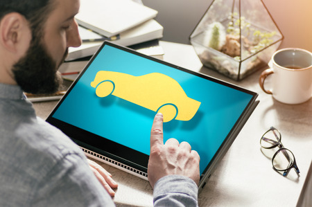 Bearded man with laptop at his desk. He presses on the car icon. Concept of car rent, buying, insurance in web. Image Foto de archivo