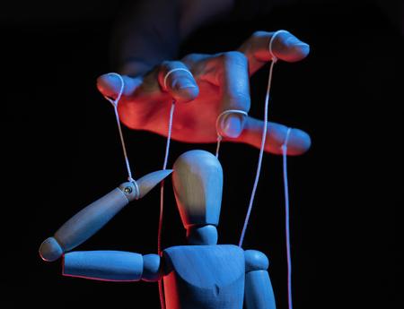 Konzept der Kontrolle. Marionette in menschlicher Hand. Objekte werden auf rotem und blauem Licht eingefärbt. Standard-Bild
