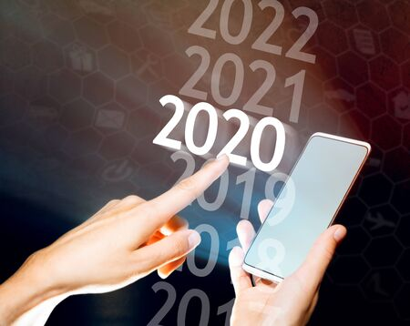 Woman hand select 2020 on her smartphone. New 2020 year in high tech. Stok Fotoğraf