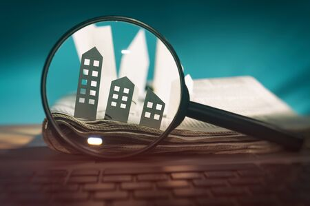 Magnifying glass in front of an open newspaper with paper houses. Concept of rent, search, purchase real estate. Stok Fotoğraf - 126647941