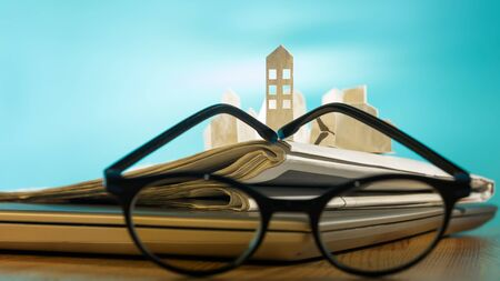 Magnifying glass in front of an open newspaper with paper houses. Concept of rent, search, purchase real estate. Stok Fotoğraf - 126647978