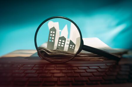 Magnifying glass in front of an open newspaper with paper houses. Concept of rent, search, purchase real estate. Stok Fotoğraf - 126647981