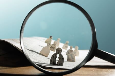 Business recruitment or hiring photo concept. Looking for talent. Icons of candidates are standing on open newspaper under magnifier. Stok Fotoğraf