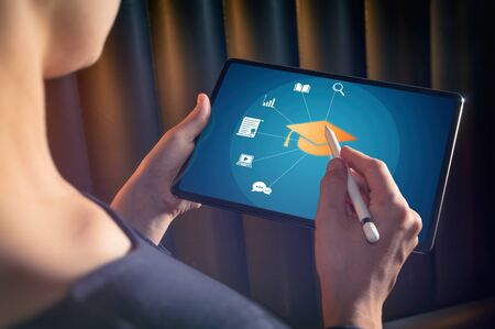 The woman selects graduation hat icon on her tablet pc. Concept of e-learning, online course, webinar. Stok Fotoğraf - 128338942