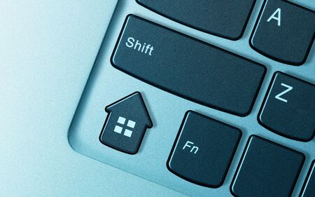 Keyboard button in form house as a metaphor for real estate buying, selling, booking.