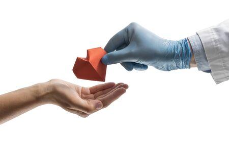 Ręka lekarza daje kobiecie serce z czerwonego papieru. Obraz na na białym tle. Koncepcja zbawienia, darowizny, pomocna dłoń.