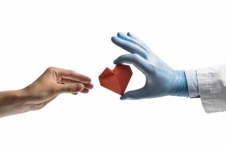 Doctor's hand gives a red paper heart to a woman. Image on isolated white background. Concept of salvation, donorship, helping hand. Stok Fotoğraf - 128338961