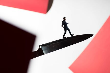 The concept of risk. A man in a business suit walks on the blade of the knife. Image.