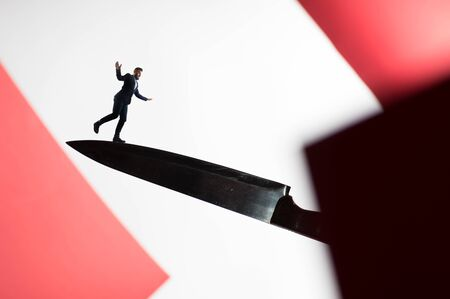 The concept of risk. A man in a business suit walks on the blade of the knife. Image. Stok Fotoğraf - 130680366