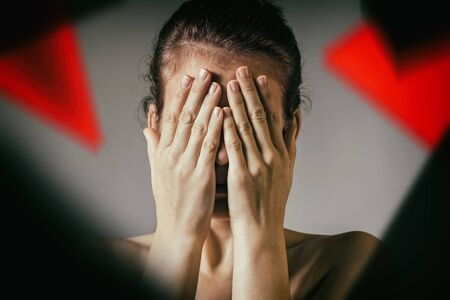 The woman covers her face. Concept of suffering, grief, fear, etc.