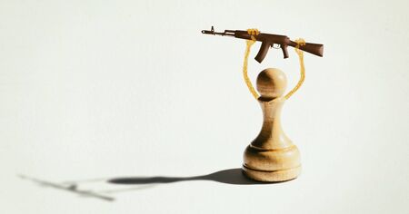 A pawn holds a gun above his head. The concept of political and religious manipulation of people. Stok Fotoğraf - 130680222