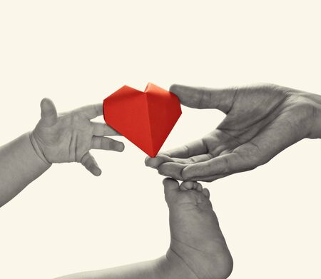 Baby to takes red paper heart from mom's hands. Concept of love, care, adoption. Black and white image.  Isolated Stok Fotoğraf - 130680156
