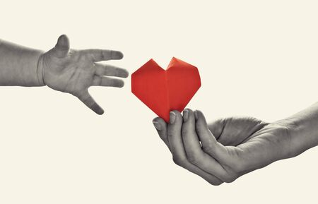 Baby to takes red paper heart from mom's hands. Concept of love, care, adoption. Black and white image. Isolated Stok Fotoğraf - 130680158