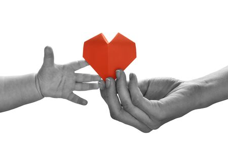 Baby to takes red paper heart from moms hands. Concept of love, care, adoption. Black and white image.  Isolated