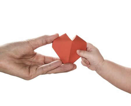 Baby to takes red paper heart from mom's hands. Concept of love, care, adoption. Color, isolated image. Stok Fotoğraf - 130680105