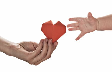 Baby to takes red paper heart from mom's hands. Concept of love, care, adoption. Color, isolated image. Stok Fotoğraf - 130680107
