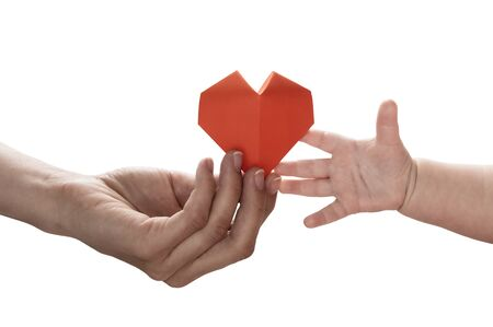 Baby to takes red paper heart from moms hands. Concept of love, care, adoption. Color, isolated image. Stok Fotoğraf