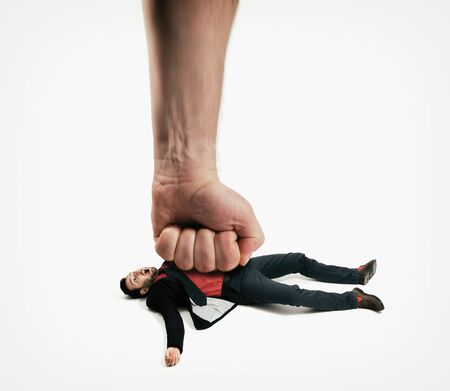 The big human fist bring down the man off his feet. Concept of unexpected problems which gets knocked down. Stok Fotoğraf - 130967301