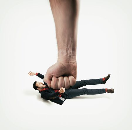 The big human fist bring down the man off his feet. Concept of unexpected problems which gets knocked down. Stok Fotoğraf - 130967308