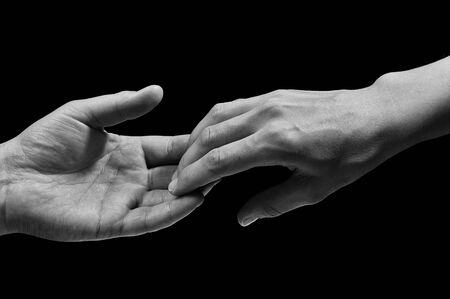 Black and white photo of two hands at the moment of breakup. The concept of  breakup. On black isolated background. Image.