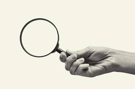 Female hand holding the magnifying glass on isolated background. Black and white image.