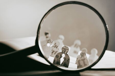 Business recruitment or hiring photo concept. Looking for talent. Icons of candidates are standing on open newspaper under magnifier. 版權商用圖片