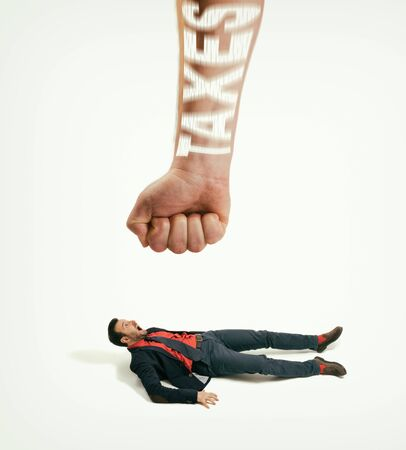 The big human fist with text - taxes bring down the man off his feet. Concept of heavy taxes. Image.