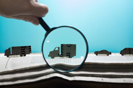 Magnifying glass in front of an open newspaper with paper cars. Concept of car rent, search, purchase and cargo transportation. Stockfoto