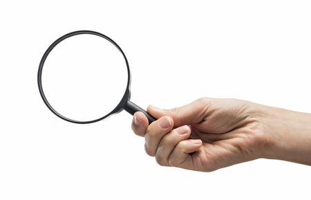 Mano femminile che tiene la lente d'ingrandimento su fondo bianco isolato. Archivio Fotografico