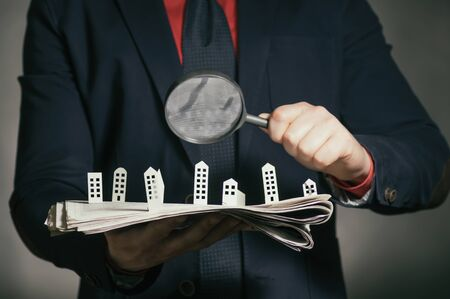 De man houdt een krant met papieren huisjes voor je. Concept van onroerend goed, woningbouw. Stockfoto