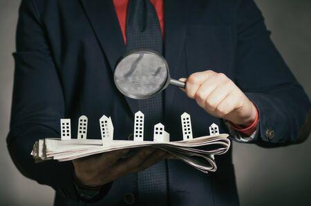 El hombre sostiene un periódico con casas de papel frente a ti. Concepto de bienes raíces, construcción de viviendas. Foto de archivo