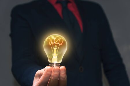 The businessman holds a lamp with a new 2020 year in front of yourself. Concept of a new ideas new discoveries.