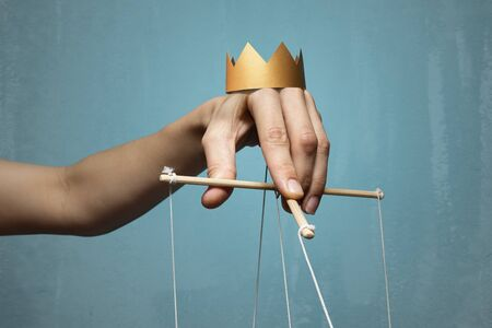 Concept of manipulation. Hand with crown holds strings for manipulation. Image