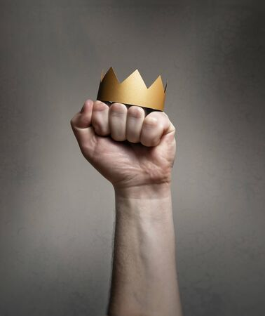Concept of power. Golden crown on a man's fist.