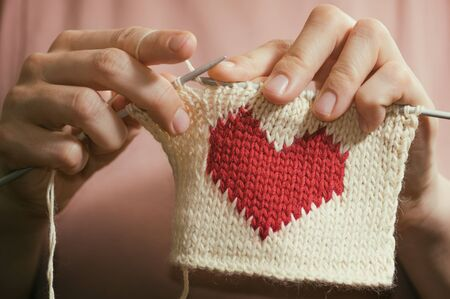 Concept of love and concern. Woman knitting the red heart for her loved one. Valentines postcard. Stock Photo - 137446004