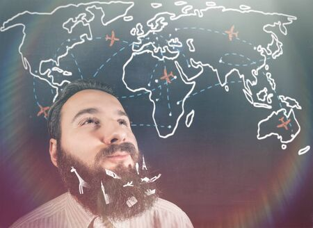 Portrait of brooding bearded man against a background of a chalk board with world map and planes.