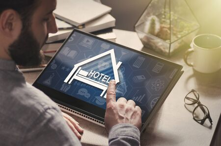 Man with laptop on his desk. He presses on the hotel icon. Search and online reservation of hotel. Standard-Bild