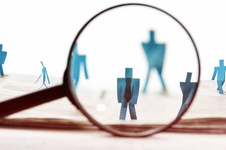 Business recruitment or hiring photo concept. Looking for talent.  Figure of candidates are standing on open newspaper under magnifier.