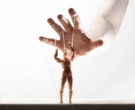 Concept of control. Marionette in human hand. Image on white.