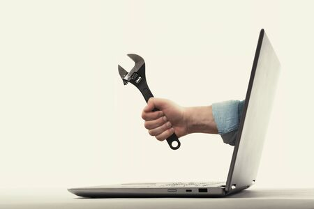 The human hand with  black wrench stick out of a laptop screen. Concept of technical support.