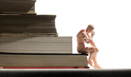 Puppet of human is sitting on stack of books. Concept of learning.