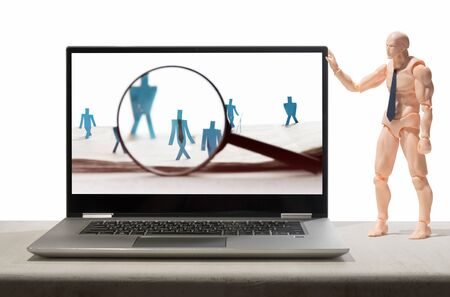 Puppet of human holds open laptop with figures of candidates are standing on open newspaper under magnifier.