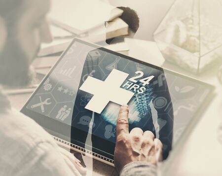 Image with double exposure. Man with laptop on his desk presses on the icon of medical care and silhouette of doctor. Concept of the round-the-clock medical care. Reklamní fotografie