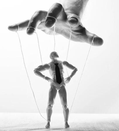 Concept of control. Marionette in human hand. Black and white image.