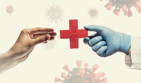 Doctor's hand gives a red paper cross  to a woman. Image on background with coronavirus covid-19. Concept of medical treatment during the pandemic covid-19