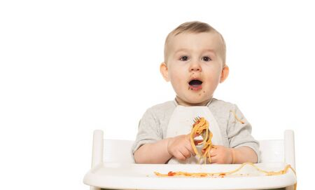Portrait of funny baby boy that eats spaghetti in tomato sauce on white isolated background.