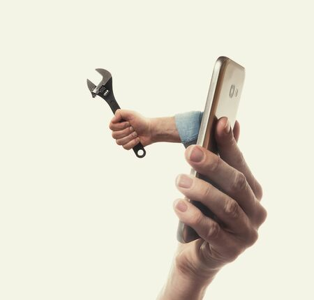 The human hand with black wrench stick out of a smartphone screen. Concept of technical support. Stockfoto